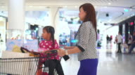 Girl and Mother Riding market cart In Shopping Mall