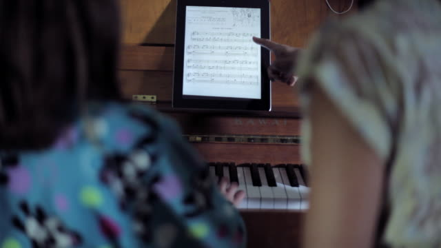 MS TU TD Girl and Woman practicing piano, reading music sheet from iPad / Santa Monica, CA, United States