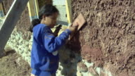 MS Girl (6-7) applying adobe mud mixture to wall of straw house under construction, Grass Lake, Michigan, USA