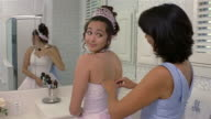 Girl applying makeup while mother zips up her Quinceanera dress