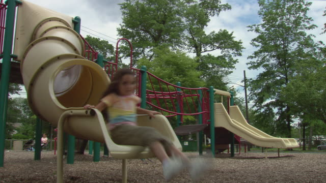 MS Girl arriving at bottom of slide in public park/ Boy coming out right behind her and laughing/ Boy and girl getting up and running/ Fanwood, New Jersey