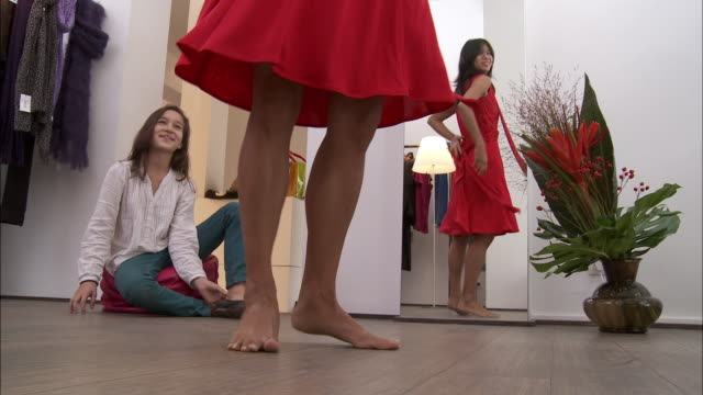MS Girl (10-11) assisting mother trying on red dress in fitting room / Brussels, Belgium
