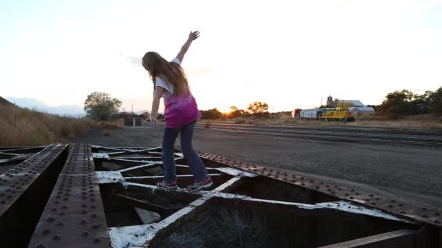 girl balancing on railroad trestle