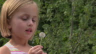 SLO MO CU Girl blowing seeds off dandelion flower / Georgia, USA