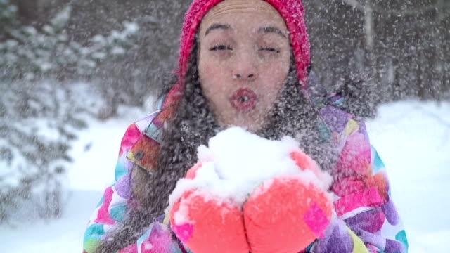 Mädchen bläst immer Schnee in Richtung der Kamera