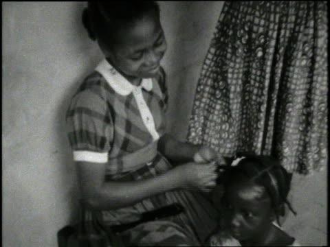 A girl braids the hair of a friend