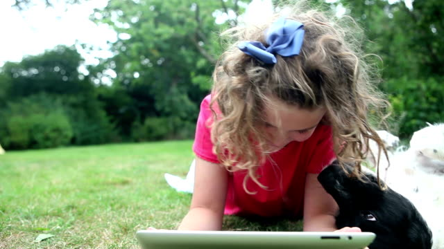 Girl browsing digital tablet being distracted by her dog