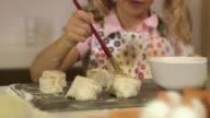 Girl brushing cinnamon bun with beaten egg Stockholm Sweden.