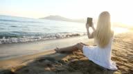 Girl capturing an image of sea horizon