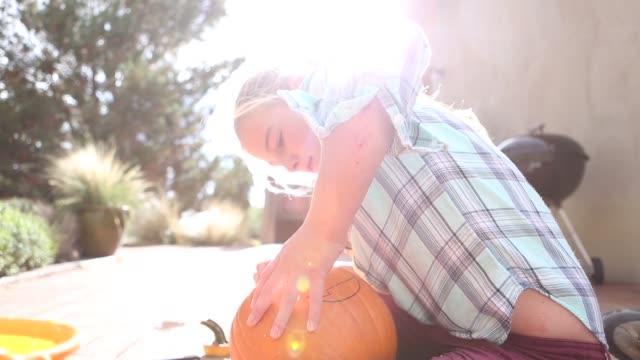 girl carving pumpkin