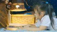 Girl child reading kids book in a tent