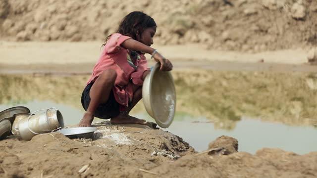 Girl cleaning utensils, Haryana, India