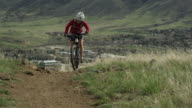 Girl climbs a steep dirt hill towards the camera on her mountain bike