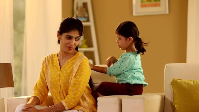 Girl combing her mother hair, Delhi, India