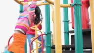 MS LA PAN Girl (6-7) crossing on monkey bars on playground / Richmond, Virginia, USA