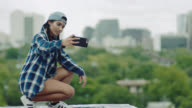 Girl crouches and takes smartphone selfie overlooking downtown Austin.