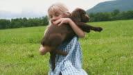 CU Girl cuddling and kissing Chocolate Labrador sitting on meadow, Sunderland, Vermont, USA