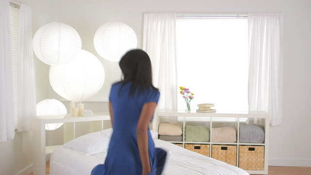 girl dancing and jumping on bed
