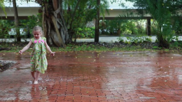 WS PAN Girl (2-3) dancing in rain and splashing in puddle / Lamy, New Mexico, USA
