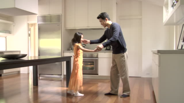 WS, Girl (6-7) dancing on father's feet in kitchen