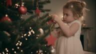 Mädchen dekorieren Weihnachtsbaum