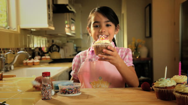 MS Girl decorating cupcake in kitchen / Los Angeles, California, USA