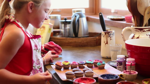 MS Girl decorating cupcakes in kitchen / Lamy, New Mexico, United States