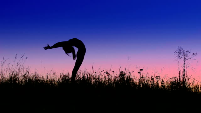 Girl does backbend exercise in evening field