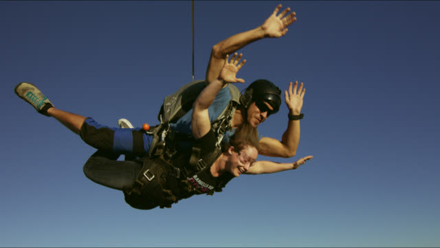 Girl does tandem skydive at sunset