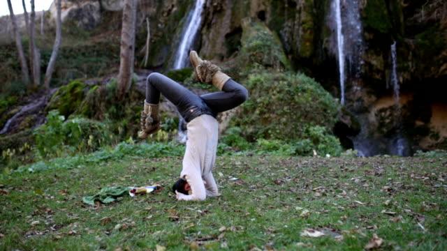 Girl Doing Sirsha-asana By Waterfall