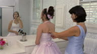 Girl dressed in Quinceanera dress applying makeup while mother adjusts her dress