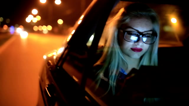 Girl driving at night in the car and working on digital tablet