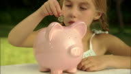 CU, Girl (6-7) dropping coins into piggy bank