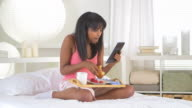 girl eating breakfast in bed while reading tablet computer