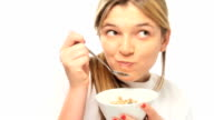 Girl eating cereal with fruit.