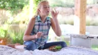 girl eating dinner on outdoor bed