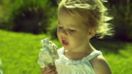 CU Girl (2-3) eating Ice Cream Cone, as ice cream falls to ground and girl begins to cry / Burbank, California, USA