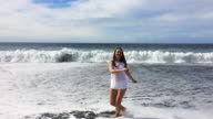 Girl enjoying and having fun in the volcanic beach of the Lanzarote island during a travel vacations with slow motion view.