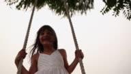 Girl enjoying rope swing, Haryana, India
