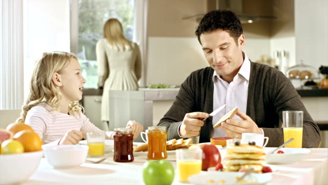 Girl explaining something to her father at breakfast