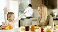 Ragazza spiegando qualcosa a sua madre sul tavolo per la prima colazione