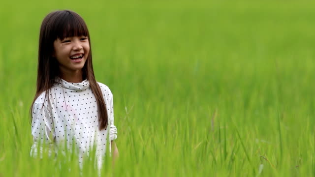 girl feeling happiness to enjoy playing at the rice field.