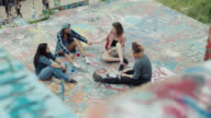 Girl friends sit and talk and fist bump on graffiti wall in urban park.