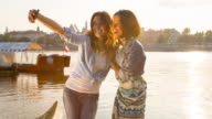 MS girl friends taking selfie photo on wooden dock by river