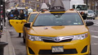 Girl getting out of a yellow taxi in front of Chelsea Market in the Meatpacking District of Manhattan