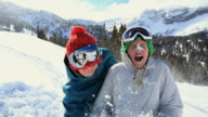 MS Girl (10-13) getting splashed with snow by boy / Alta, Utah, USA