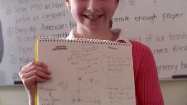 Girl giving report in front of class / smiling at camera / showing notebook with sketches and notes on frogs to camera / answering questions from other students / Gorham, Maine