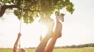 SLO MO Girl having fun swinging on tree swing