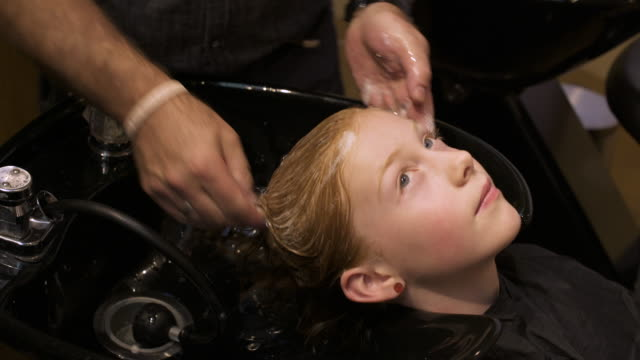 Girl having her hair washed by a hairdresser
