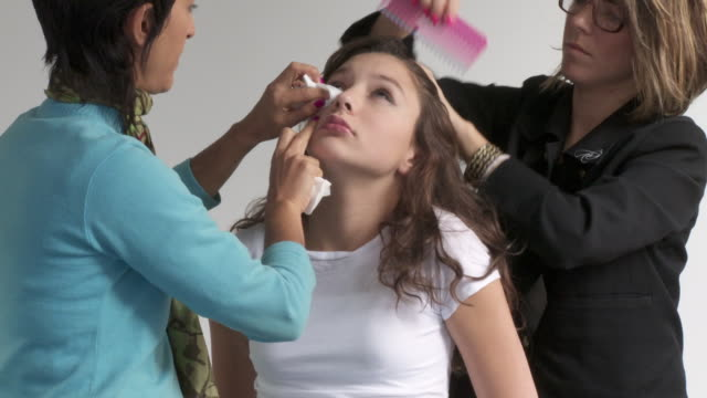 T/L, MS, Girl (12-13) having make-up removed after photo shoot